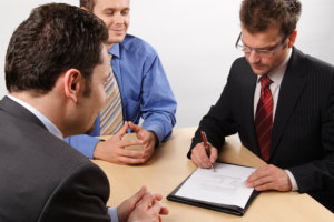 People negotiating and signing a contract